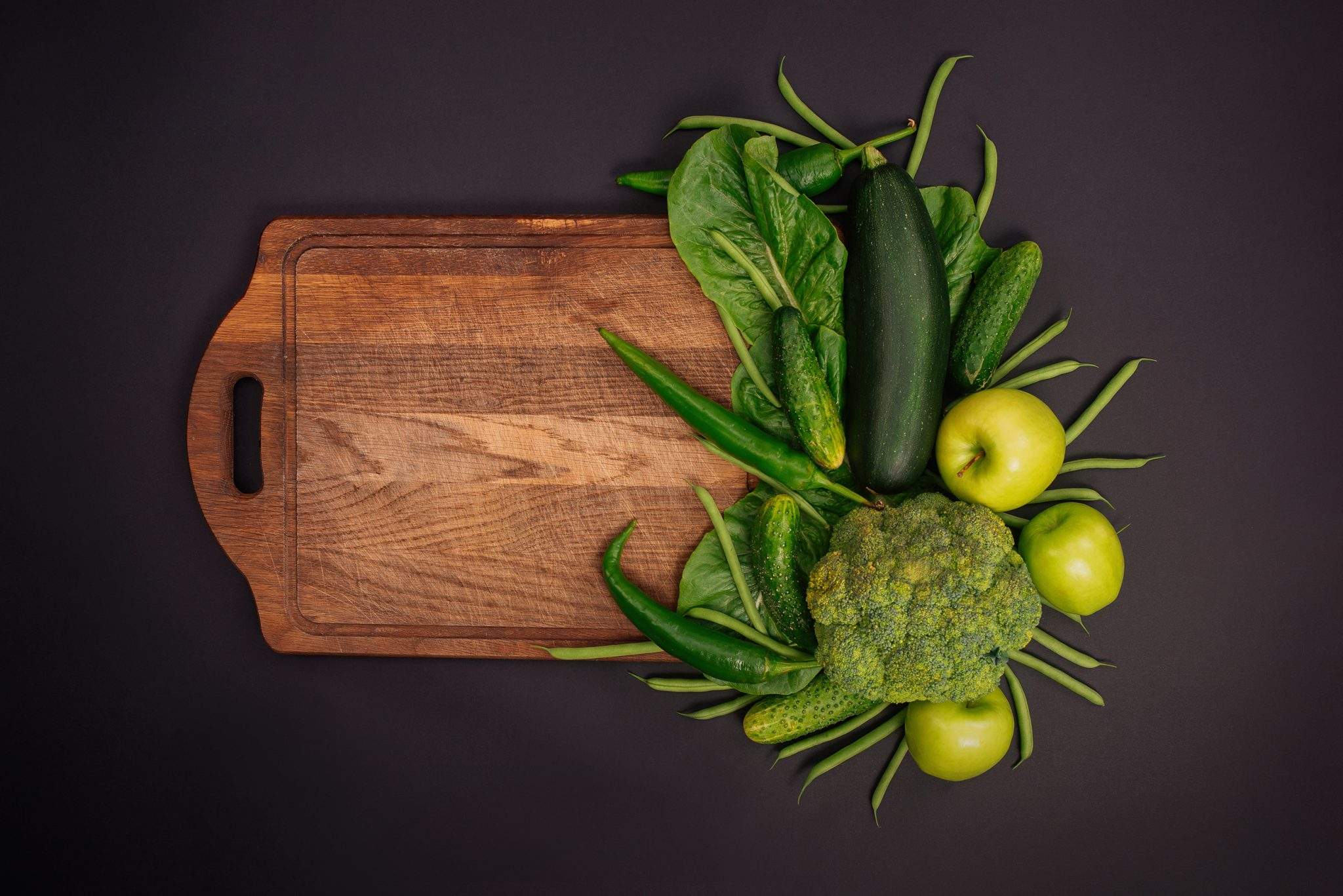 green vegetables on a black background with a board
